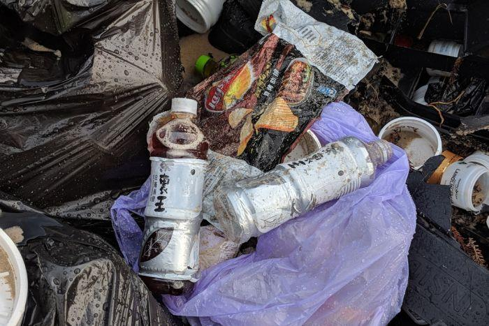 Plastic bags, bottled drinks and jars of emu oil are among the debris - photo © ABC News
